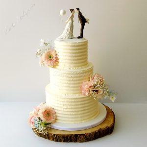 Bruidstaart Creme met bloemen en ballon topper